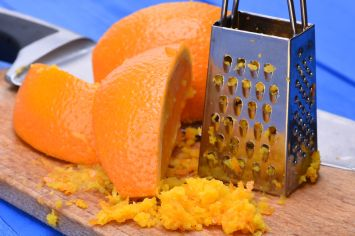 52589146 - orange fruit and orange zest with grater on wooden board